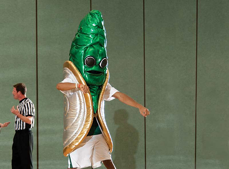 A performer in a lamé costume with big, cartoon eyes, a ridged green siphon和 a gold-accented shell dances on a basketball court