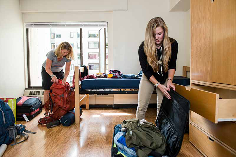 A parent helps her student move into housing
