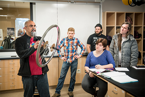Students observing instructor Krishna Chowdary demonstrate how gyroscopes work using a bicycle wheel和 rope hanging from the celling.